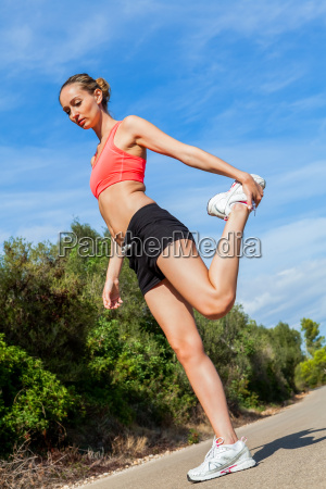 young sporty woman making stretchable streching