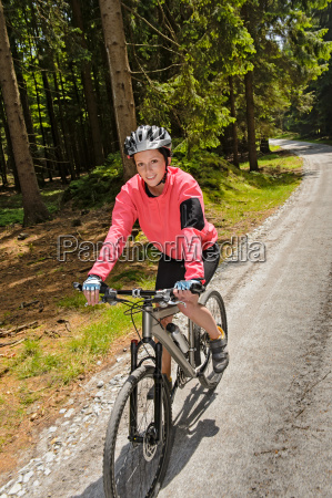 woman mountain biking in sunny forest