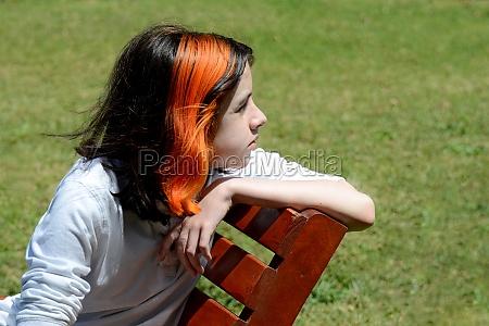 boy sitting on bench in grass