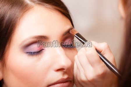 makeup artist applying with brush cosmetic