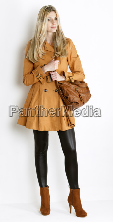 standing woman wearing coat and fashionable