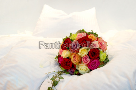 bridal bouquet on a bed