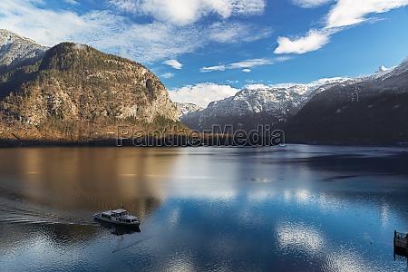 lake hallstatt in alps with ferry