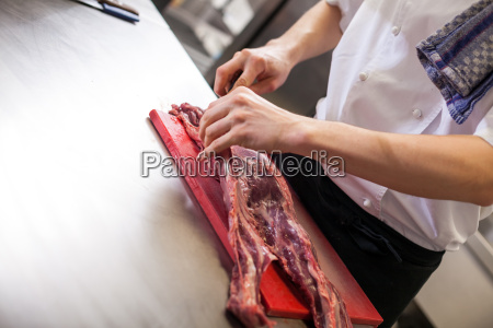 cook cuts fresh red meat in