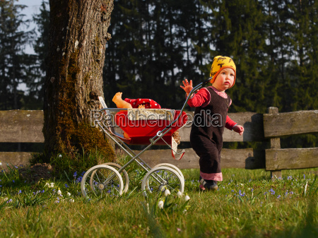 child with dolls cart