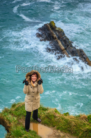 woman standing on rock cliff by