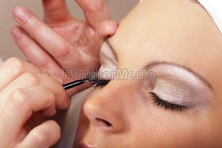beautician at makeup of the eyelids