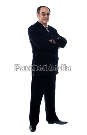 handsome old manager standing with arms