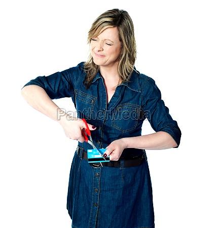 beautiful woman cutting her credit card