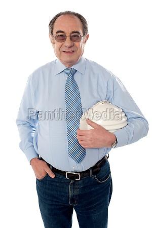 senior architect holding hard hat