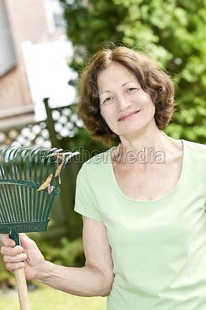 senior woman holding rake