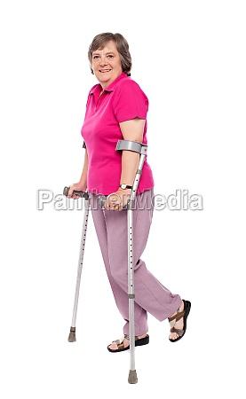 smiling senior woman walking with crutches