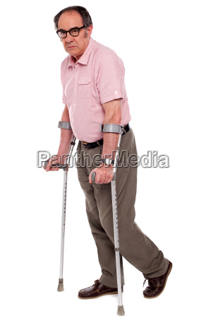depressed senior male with two crutches