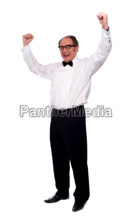 excited senior man posing with raised