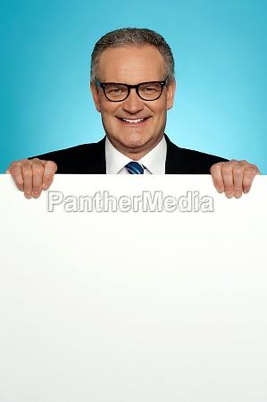 corporate man standing behind big blank
