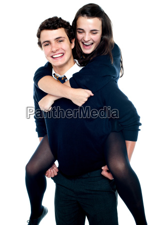 cheerful boy carrying school friend on