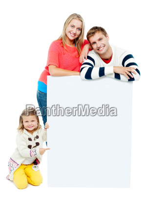 portrait of happy family presenting blank