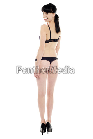 sexy brunette in black bikini turning