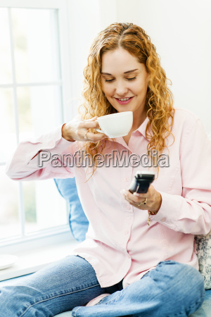 woman dialing phone and drinking coffee