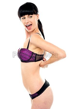 ravishing woman unhooking her brassiere