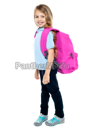 happy little girl carrying school bag