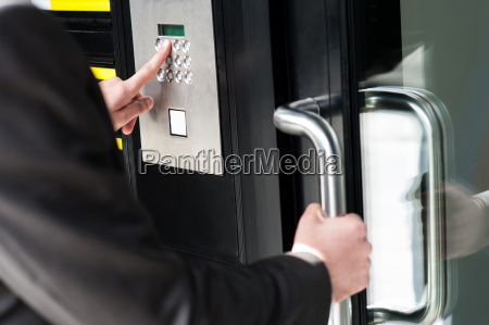 man entering security code to unlock