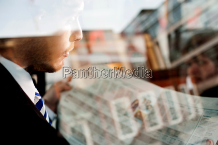 male passenger reading newspaper in taxi