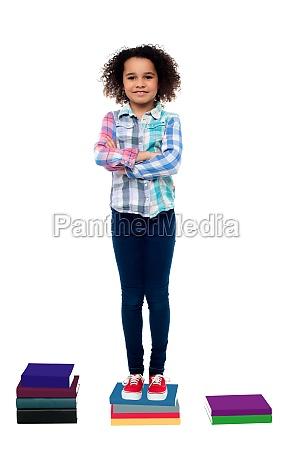 confident school child standing on books