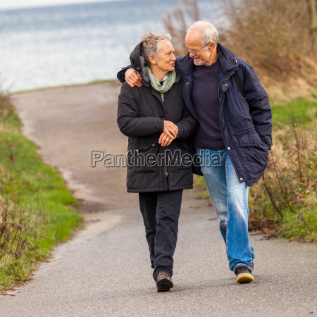 older happy couple takes a walk