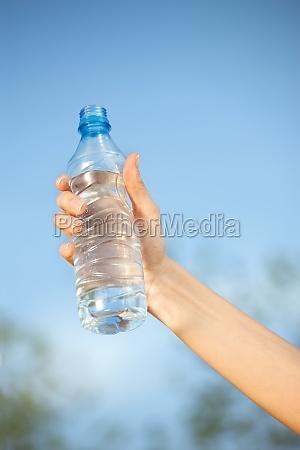 hand holding plasic bottle of water