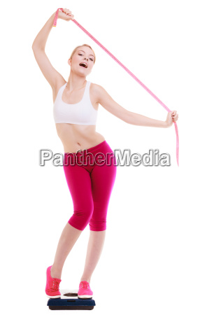 woman with tape measure on scale