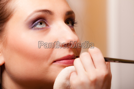 makeup artist applying brush with lipstick