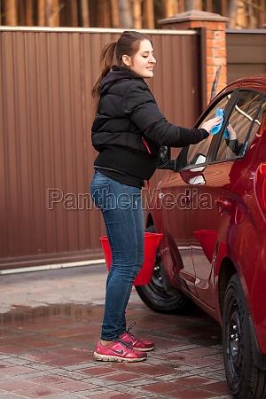 woman washing red car at yard