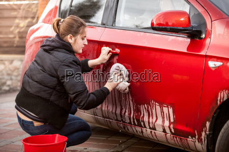 woman cleaning car door from mud