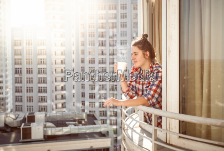 woman drinking coffee and smoking out