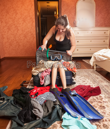 woman packing girl in big suitcase