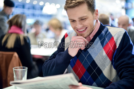 stylish man reading newspaper at cafe