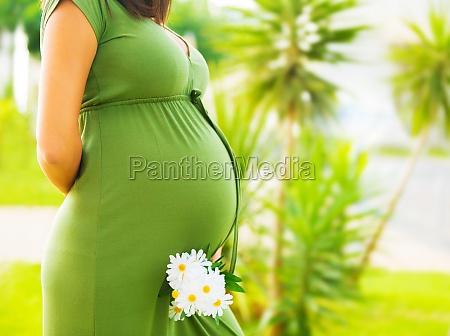 pregnant woman enjoying summer park