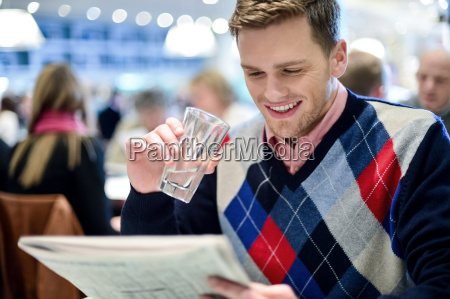 young man reading newspaper at cafe