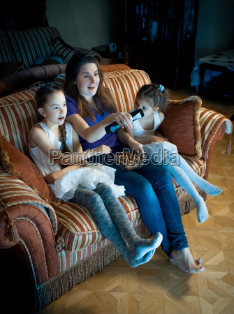 mother and two daughters watching tv