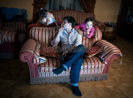 two daughters disturbing father while watching