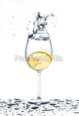 lemon splashing into glass of water