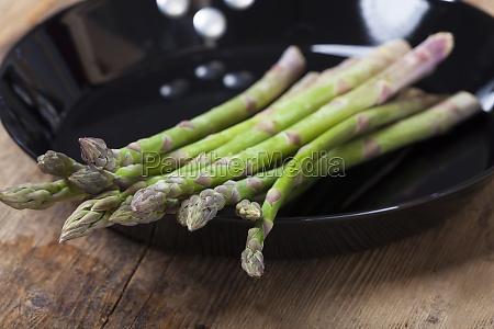 raw green asparagus in a pan
