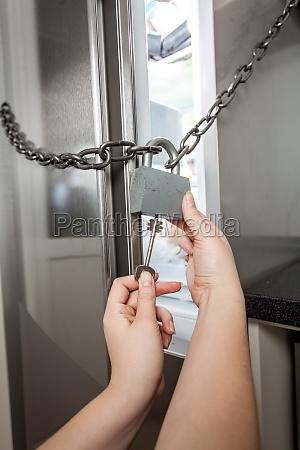 woman opening lock on fridge with