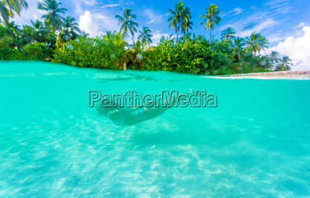 female diving near exotic island