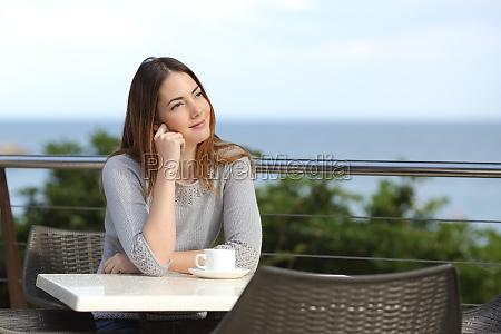 woman pensive sitting in a terrace