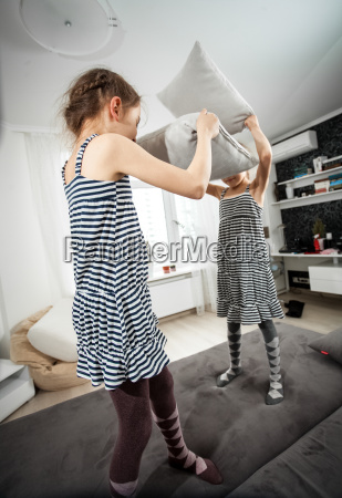 shot of girls fighting with pillows