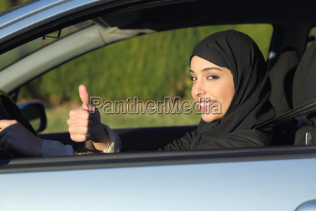 happy arab saudi woman driving a