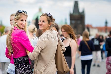 two pretty young women window shopping