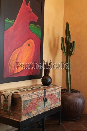 large painting above old wooden chest